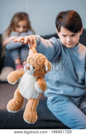 Boy Holding Teddy Bear While Offended Girl Sitting On Sofa Behind