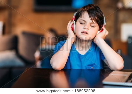 Portrait Of Concentrated Little Boy Listening Music In Headphones