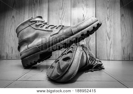 male militarly style leather boots used male fashion shoes on floor wood background. high contrast filter added with black and white color