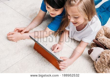 little boy and girl playing with digital tablet while lying on carpet at home