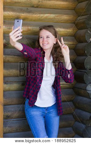 Cheerful young girl with a smile standing in jeans t-shirt and checkered red shirt posing photographing herself on the phone