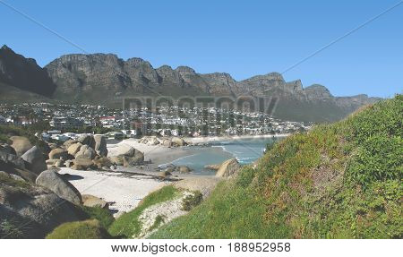 FROM CAMPS BAY, CAPE TOWN, SOUTH AFRICA, WITH A GRASS BANK IN FORE GROUND AND A MOUNTAIN IN THE BACK GROUND 24dfty