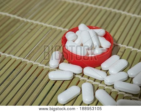 Group of Paracetamol medicine tablets on bamboo floor