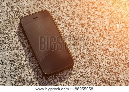 Black smartphone lying on a concrete slab in the sunlight.