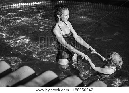 Happy Active Mother And Daughter In Swimming Pool Playing