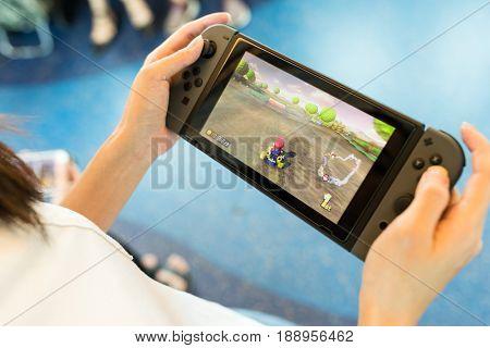 Hong Kong, 19 May 2017 -:Woman holding a Nintendo Switch with playing mario kart 8