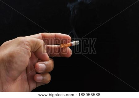 hand holding cigarette and smoke on black background