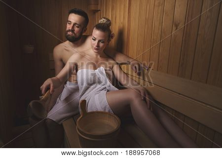 Young couple enjoying the sauna session together and relaxing