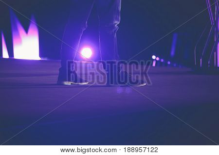 Man feet in shoes and jeans on stage. Back light. Stand up concert or conference speaker concept