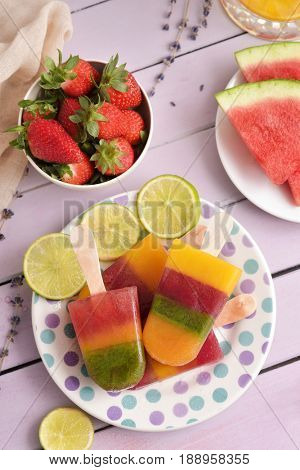 high-angle shot of a ceramic plate with some different homemade natural ice pops next to some different pieces of fruit, such as strawberries or watermelon, on a rustic pink table