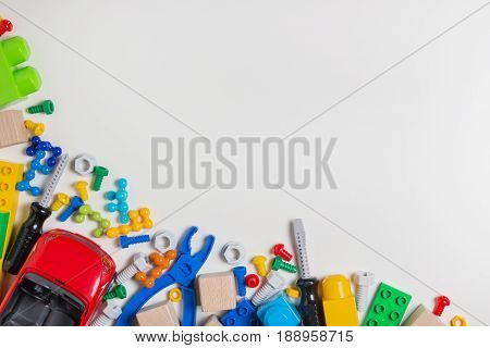 Colorful kids toys frame. Plastic toy construction tools, car, blocks, cubes on white background as frame. Top view.
