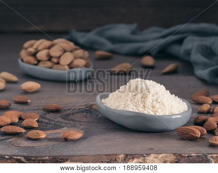 Almond powder in gray trendy plate and almonds on dark wooden table. Almond flour and peeled kernel almonds. Copy space.