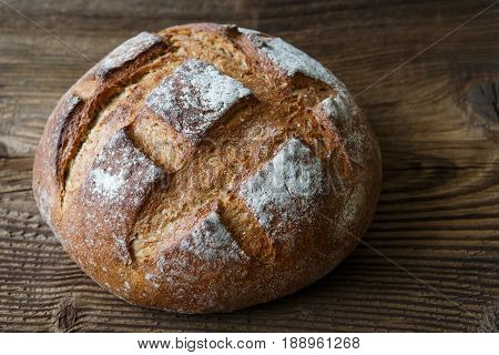 A Freshly Baked Rustic, Loaf Of Bread On An Old Wooden Table