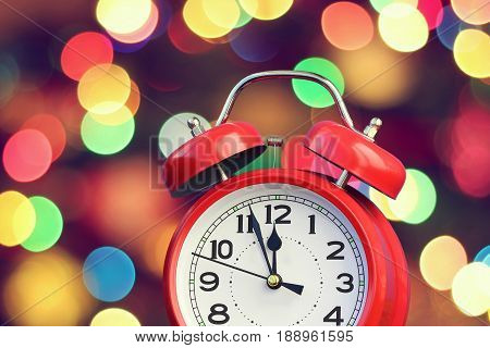 Red retro alarm clock at twelve o'clock on blurred Christmas background with bokeh. Midnight midday. Minutes about New year.