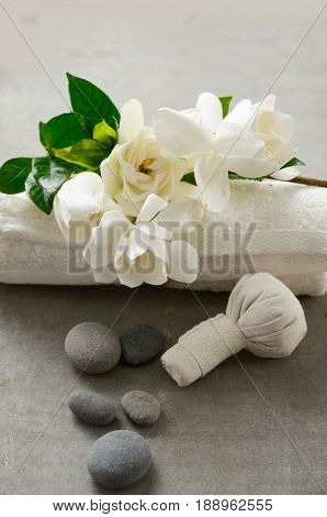 gardenia on towel with gray stones with herbal ball on grey background.