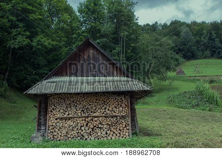 wooden house with accurately precisely gathered together firewood logs at the mountains