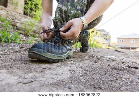 A Man In Camouflage Pants Ties Shoes. Military
