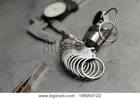 Tools Of Jewellery. Jewelry Workplace On Metal Background. Finger Sizing For Rings, Beam Compass, Pi