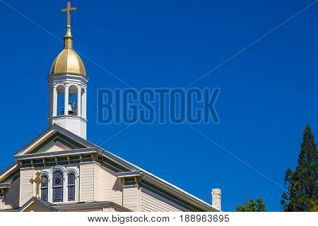 Church Steeple With Gold Dome & Cross Against Blue Sky