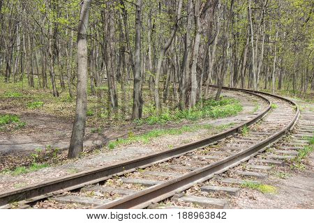 abandoned curved railroad at the forest among trees