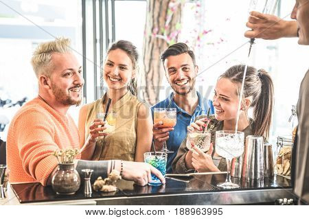 Group of friends drinking cocktails and talking at restaurant - Beverage concept at fashion mixology bar having fun drunk moments - Barman pouring liquor on side - Focus on young smiling women