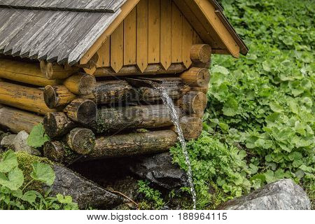 Natural source of spring water in forest flowing from a wooden well