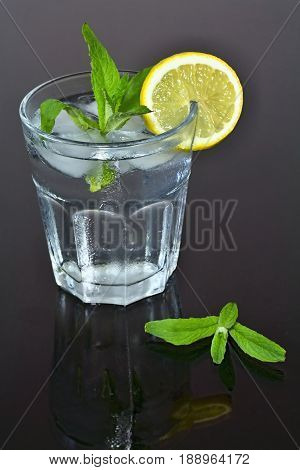 Fresh mint. Water in glass. Lemon and mint. Refreshing drink. Detoxification cure. Fresh water and forest mint.