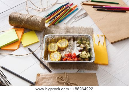 Healthy lunch of artist. Diet concept. Take away food in foil boxes, papers and pencils on working table of creative person or art student. Meat with vegetables, top view on white wood