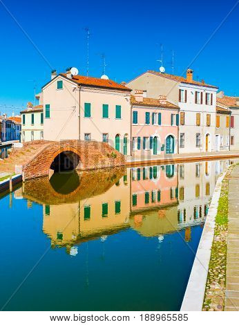 View of the old Italian town with colorful houses reflected in water. The small Italian town of Comacchio - province of Ferrara. Empty street with canal with no boats and the old residential houses