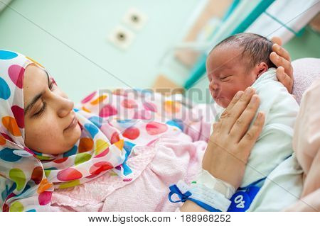 mother carrying her child in hospital bed
