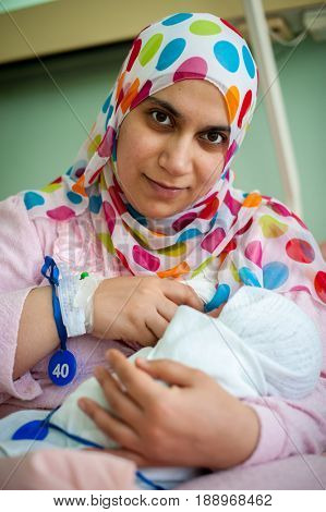 Muslim woman first feeding her new born baby from her breast