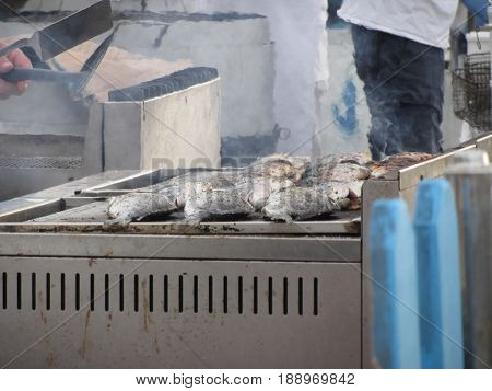 Grilling fish outdoors with smoke emerging from the grill