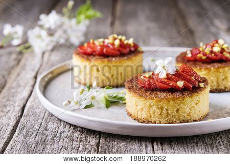 Pieces of homemade semolina cake with strawberry and pistachio decorated flowers of cherry on a rustic vintage wooden table. Selective focus