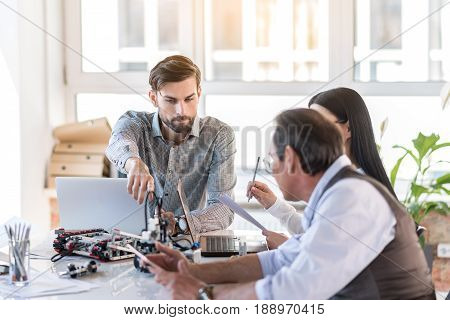 Tech progress. Selective focus on handsome bearded man is sitting with colleagues at table. He is pointing to robot with interest