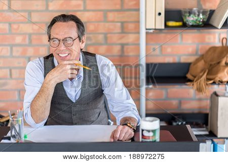 Good mood. Positive pleasant mature man is sitting at table while touching his chin. He is looking aside with smile. Portrait