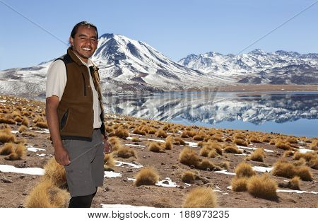 SAN PEDRO DE ATACAMA-SEPTEMBER 21 2014: Quechua native man smiles before the camera in a wonderful Andean landscape in northern Chile. The highland lagoons on september 21, 2014
