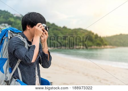 Young Asian backpacker man take photos of beautiful tropical beach and sea by camera background for summer holiday vacation time or travel photography concepts
