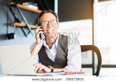 Always in touch. Portrait of joyful pleasant mature man is sitting at table and typing on laptop while communicating on smartphone with smile