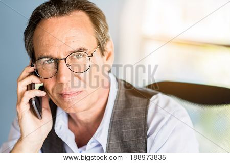 Important call. Close up portrait of confident concentrated businessman is sitting at table and talking on smartphone. He is looking at camera thoughtfully