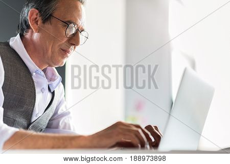 Involved in project. Serious pleasant mature man is typing on laptop intently while working in office. Copy space in the right side