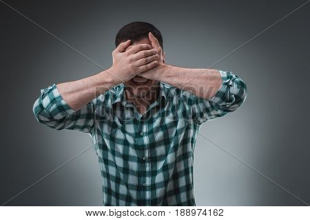 Man covering his eyes with hand, casual clothing. Face palm, shame, problem, trouble, ignorance concept.