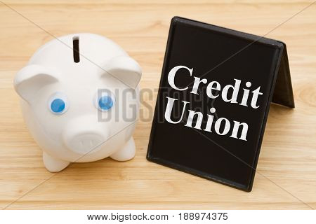 Banking using a credit union A piggy bank on a desk with chalkboard with text Credit Union