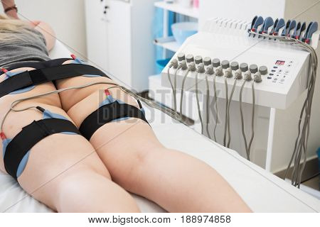 Body treatment: middle aged woman getting getting electro stimulation therapy to her buttocks