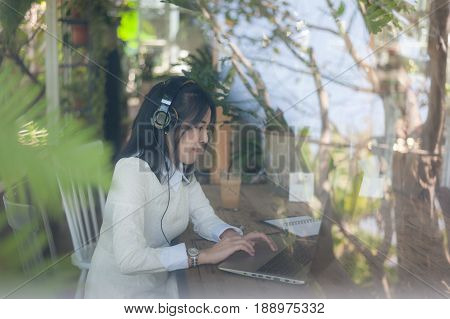 Young attractive Asian woman listening music while working online with laptop computer in coffee shop. Freelance worker and self-employed business activity concept