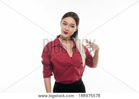 Young attractive tan skin Asian woman wear red shirt in good feeling action. Studio scene of woman with positive emotion with copy space