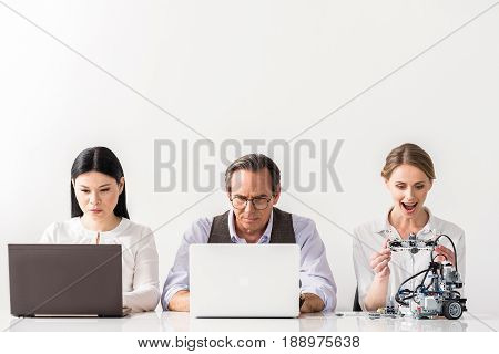 Involved in project. Portrait of serious colleagues are working on laptops with concentration while cheerful woman is holding detail of robot and expressing admiration. Isolated background