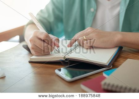 Asian freelancer with casual cloths writing on notebook in coffee shop. Outsource worker lifestyle and activity on workday