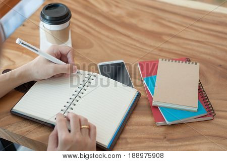Left-handed Asian freelancer with casual cloths writing on notebook in coffee shop. Outsource worker lifestyle and activity on workday