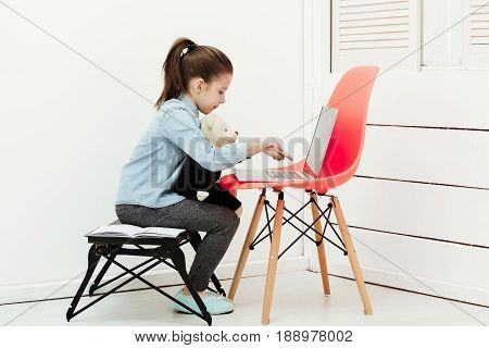 education and playing. Cute small little girl with hair ponytail sitting and typing on laptop computer on orange chair with adorable teddy bear soft toy on knees in white room at home. Childhood and technology