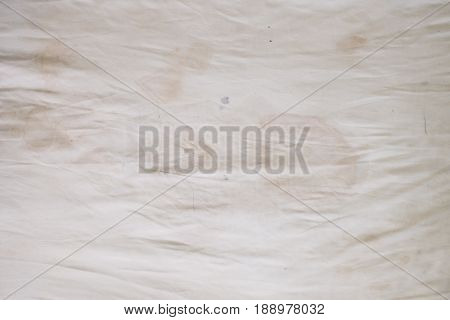 Body oil stains, odors and stains, other dirt on white bedding sheet, unclean bed sheet